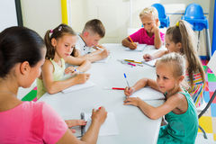 Kids learning to write on lesson in elementary school class. Glad diligent kids learning to write on lesson in elementary school class Royalty Free Stock Images