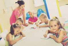 Kids learning to write on lesson in elementary school class. Glad smiling cheerful kids learning to write on lesson in elementary school class Stock Image