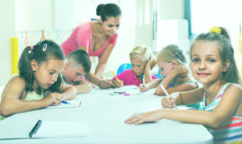 Kids learning to write on lesson in elementary school class. Smiling cheerful diligent kids learning to write on lesson in elementary school class Royalty Free Stock Photo