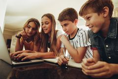 Kids learning together on a laptop stock images