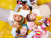 Kids on  leaves. Laughing kids on autumnal leaves Stock Photo