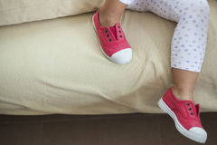Kids legs hanging the sofa. Royalty Free Stock Images