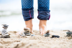 Kids Legs and Stones Pyramids on Sand. Sea in the background Stock Images
