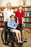 Kids in Library - Disabilities. Group of teens in the library - one is in a wheelchair, one is on hand crutches Royalty Free Stock Image