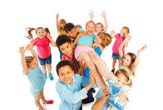 Kids lifting popular classmate and cheering. Funny portrait of kids lifting a winner isolated on white royalty free stock image