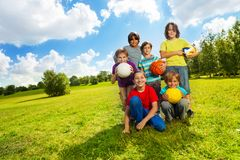 Kids like sports. Group of very happy six boys, team sitting on the grass with balls and smiling, on sunny summer day Stock Images