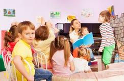 Kids listen to teacher reading book in class Stock Photos