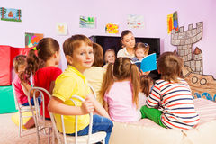 Kids listen to teacher storytelling reading book Stock Photos