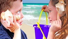 Kids Listening to Shells Stock Photography