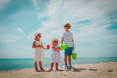Kids - little boy and girls- play with sand on beach. Family tropical vacation stock photography