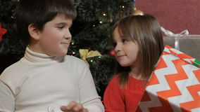 Kids look at their christmas gifts. Little kids looking at their christmas gifts near the christmas tree. Little brown-haired girl holding big striped gift box stock footage