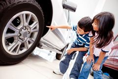 Kids looking at car wheels Royalty Free Stock Photography