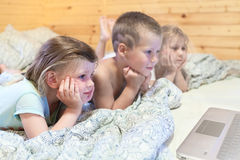 Kids looking at computer monitor while laying in bed Stock Photography