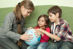 Kids looking at globe Stock Images