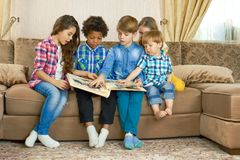 Kids looking through photo album. Children in the room royalty free stock image