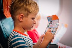Kids looking at safety instruction in flight. Kids - little boy and girl-looking at safety instruction in flight, safety royalty free stock images