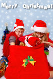 Kids looking into santa`s sack for christmas gifts. Young boy and girl in red hats looking into santa`s sack for favorite christmas gifts Royalty Free Stock Photos