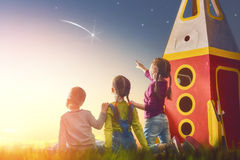 Kids looking at the sky. Children playing with toy rocket and dreaming of becoming a spacemen. Portrait of funny kids looking at the sky. Family friends games Royalty Free Stock Photography