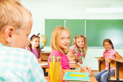 Kids looking straight while sitting at tables rows Royalty Free Stock Photo