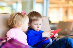 Kids looking at touch pad while travel in the Royalty Free Stock Image