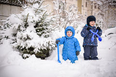 Kids and a lot of snow. playing outdoors in winter near home. two happy smiling brothers. Royalty Free Stock Photos