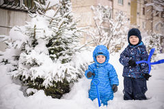 Kids and a lot of snow. playing outdoors in winter near home. two happy smiling brothers. Royalty Free Stock Photo