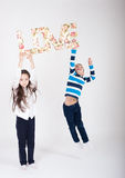 Kids love valentines day romantic boy girl pair  jump. Girl holds over her head  the word love boy jumps and tries to get it Royalty Free Stock Photography