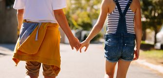 Kids in love walking on road holding hands stock photography