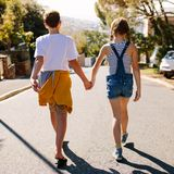 Kids in love walking on street holding their hands royalty free stock photography