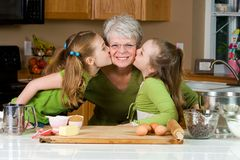 Kids loving their Grandma. Two young girls giving their Grandma a kiss on the cheek Royalty Free Stock Image