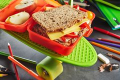 Kids lunch box with healthy cheese sandwich. Kids red plastic school lunch box with healthy cheese and tomato sandwich on wholewheat bread and sliced apple on a royalty free stock photo