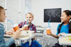 Kids at lunch break. Happy classmates with drinks having talk at lunch-break in classroom Royalty Free Stock Photos