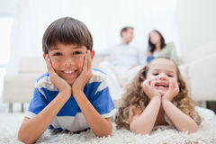 Kids lying on the carpet with parents sitting behind them Stock Images
