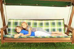 Kids lying on a garden swing. Barefoot kids - little girl lying on a boy on a wooden garden swing Royalty Free Stock Image