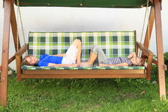 Kids lying on a garden swing. Kids - boy and girl lying on a wooden garden swing Stock Photography