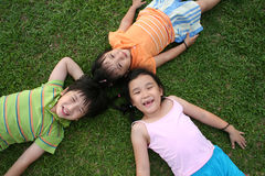 Kids lying on the grass Royalty Free Stock Photos