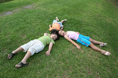 Kids lying on the grass. Happy girls and boy lying on the grass Stock Image