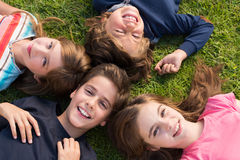 Kids lying on grass Stock Images