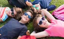 Kids lying on grass. Group of little kids lying on grass royalty free stock photography
