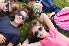 Kids lying on grass. Group of little kids lying on grass stock photo