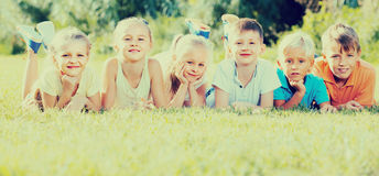 Kids lying on green grass. Happy kids lying on green grass on bright summer day Stock Photos
