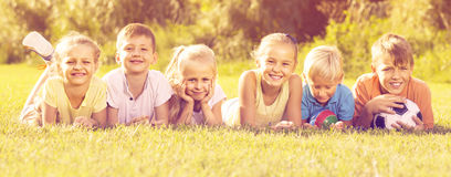Kids lying on green grass. Positive boys and girs lying on green grass on bright summer day Royalty Free Stock Images