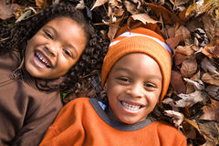 Kids lying on leaves Royalty Free Stock Photo