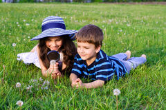 Kids with a magnifying glass on meadow Stock Images