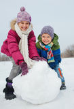 Kids make a snowman. Happy beautiful children building snowman outside in winter time Royalty Free Stock Photography