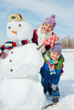 Kids make a snowman. Happy beautiful children with snowman outside in winter time Stock Image