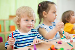 Kids making arts and crafts in day care centre together Stock Images