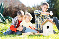 Kids making birdhouse together sitting on the grass. Oldest child teaches youngest brother to work with tools. Kids boys making birdhouse together sitting on the Royalty Free Stock Image