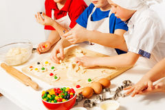 Kids making candy filled cookies on wooden desk Royalty Free Stock Image