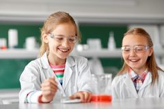 Kids making chemical experiment at school lab. Education, science, chemistry and children concept - kids or students making chemical experiment at school royalty free stock photos